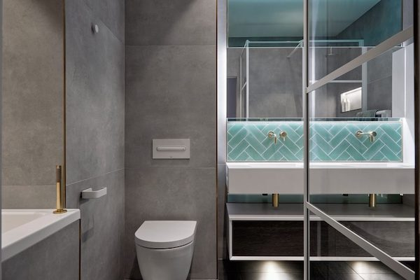 bathroom-tiled-with-large-grey-tiles-and-gold-trim