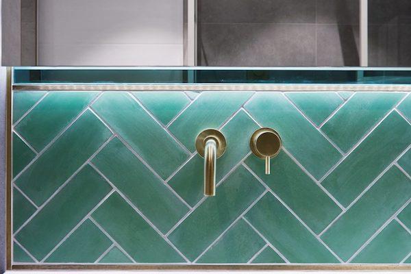 green-metro-tiles-around-bathroom-sink-with-gold-fixtures-in-home