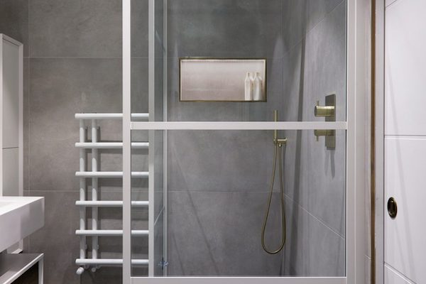 shower-screen-with-white-trim-in-front-of-shower-tiled-with-large-grey-ceramic-tiles-in-house